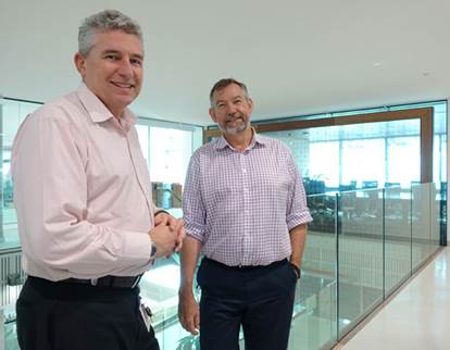 Two men in office attire standing in front of a glass wall in an office.