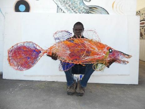 Artist Simon Norman with barramundi scuplture