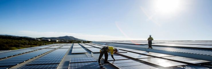 Image of two men on a large roof with solar panels